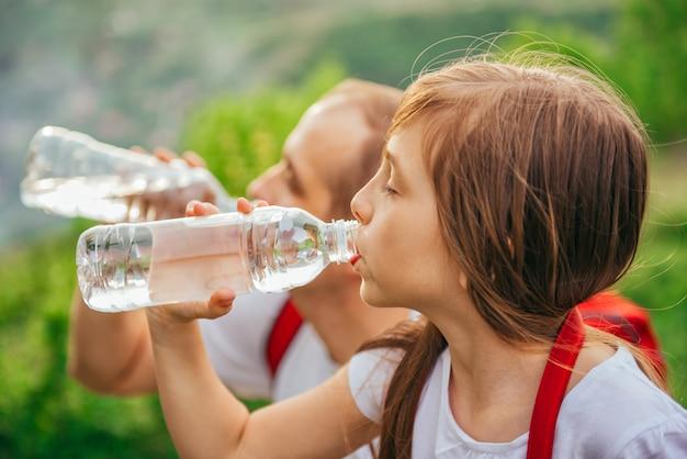 Père et fille buvant de l'eau