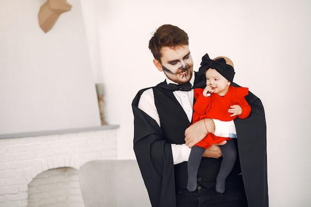 Père avec fille en costumes et maquillage. la famille se prépare à la célébration de l'halloween.