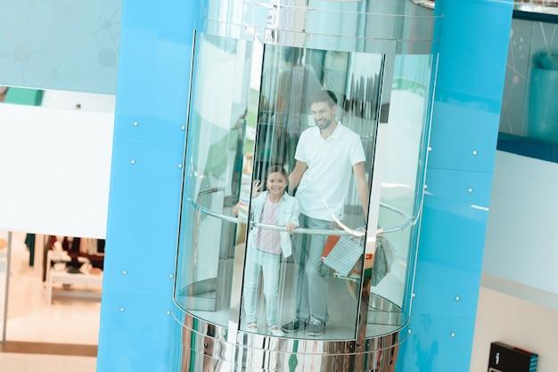Père et fille descendent dans l'ascenseur du centre commercial.