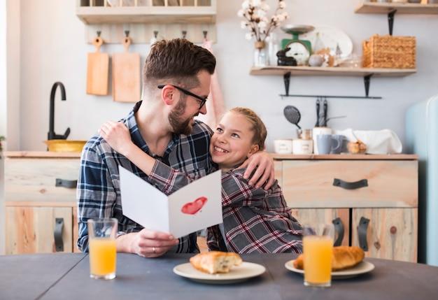 Père et fille ensemble sur la table du petit déjeuner