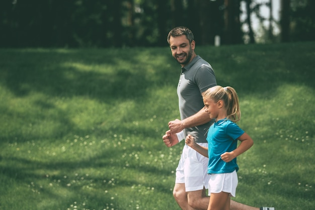 Père et fille faisant du jogging. vue latérale d'un père et d'une fille joyeux faisant du jogging ensemble dans un parc