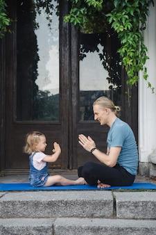 Père et fille faisant du yoga ensemble en plein air dans le parc près de l'ancien bâtiment. une famille heureuse passe du temps ensemble. concept de mode de vie sain.