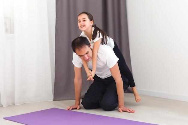 Père et fille font du fitness à la maison, entraînement sportif