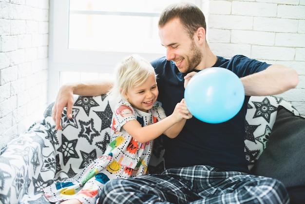 Père et fille jouant avec un ballon