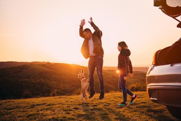 Père et fille jouant avec un chien au camping en colline