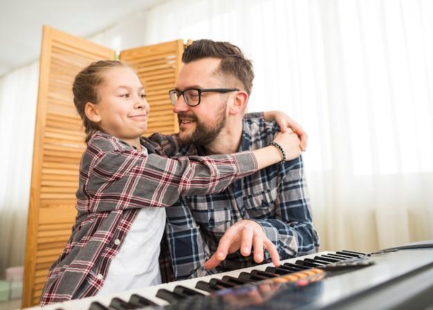 Père et fille jouant du piano