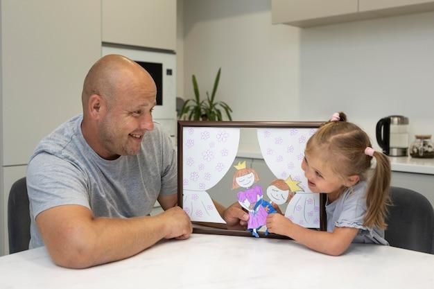 Père et fille jouant avec des marionnettes à la maison