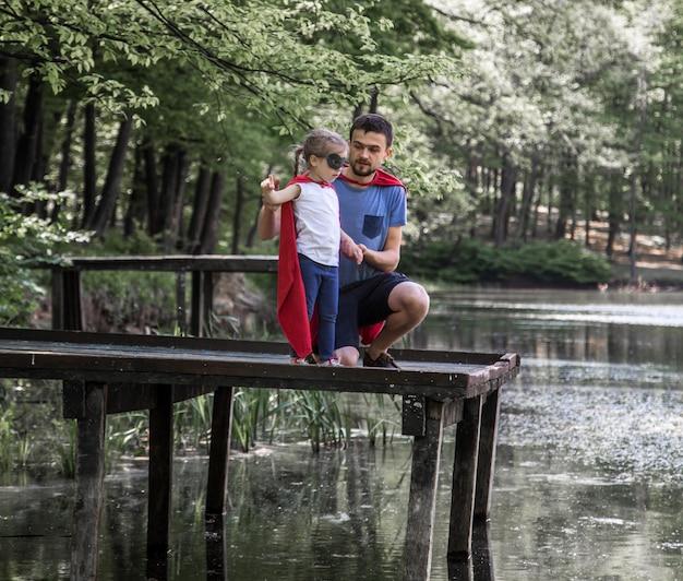 Père et fille jouant un super héros