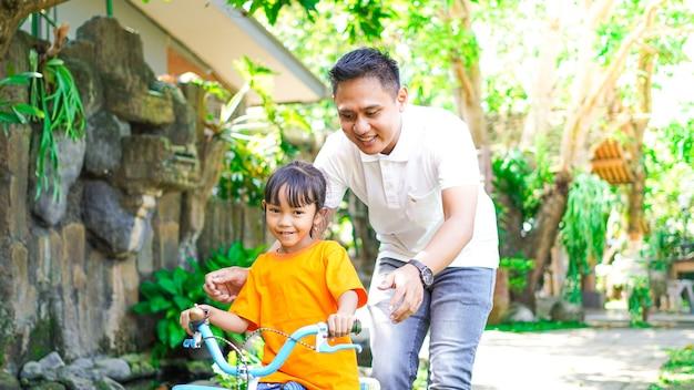 Père et fille jouant des vélos dans le parc