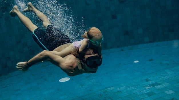 Père et fille nager ensemble dans la piscine