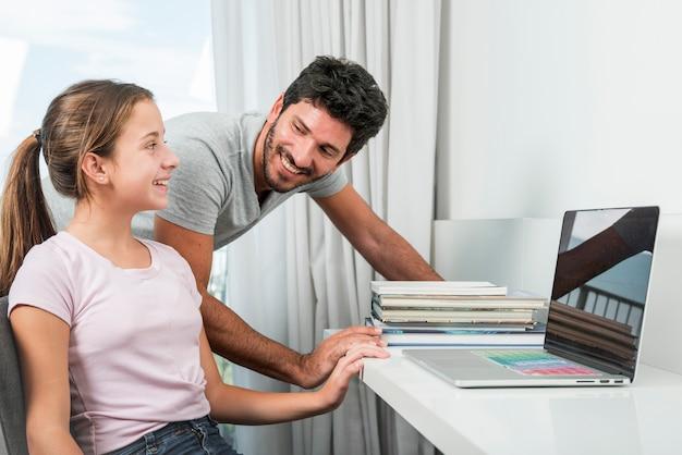 Père et fille avec ordinateur portable