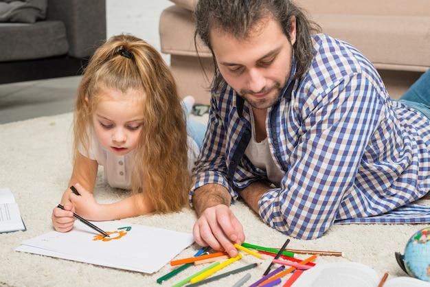 Père et fille peignant sur le sol