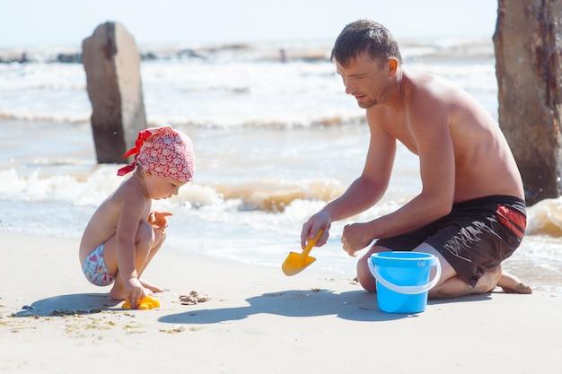 Père et fille sur la plage jouant et construisant un château de sable