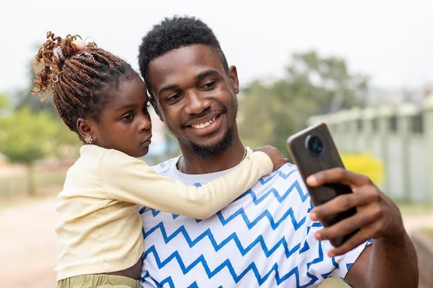 Père et fille prenant des selfies