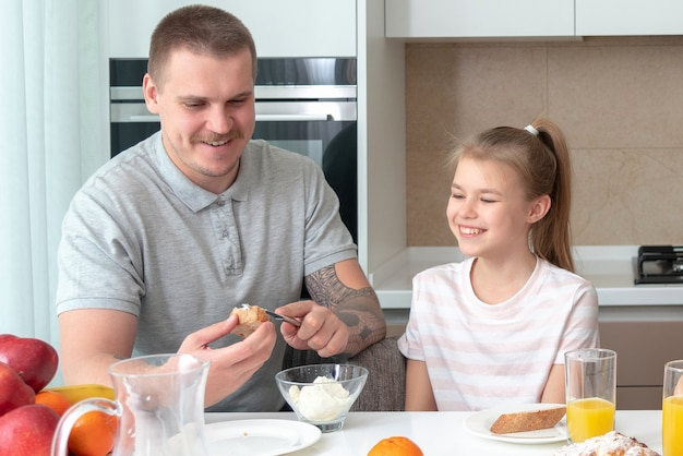 Père et fille prenant son petit déjeuner à la cuisine