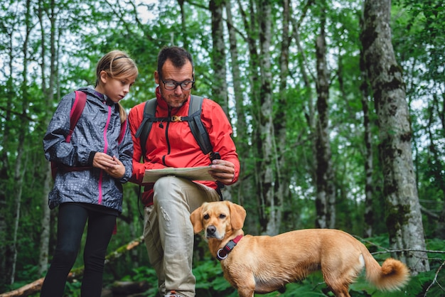 Père et fille en randonnée en forêt et en vérifiant la carte