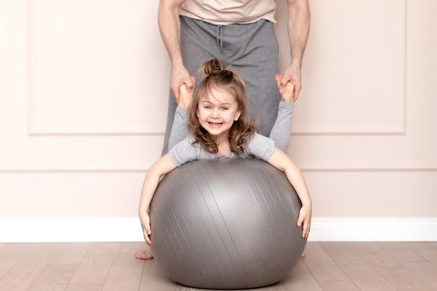 Le père et la fille s'entraînent et jouent à la maison. enfant souriant, mignon, drôle, heureux, émotionnel, adorable dans des vêtements décontractés