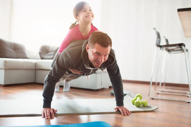 Le père et la fille s'entraînent à la maison. séance d'entraînement dans l'appartement. sports à domicile. ils font la planche à faire. fille est montée sur papa. il se lève du sol.
