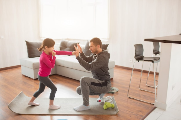 Le père et la fille s'entraînent à la maison. séance d'entraînement dans l'appartement. sports à la maison. père enseigne à garder un coup de poing. boxe ensemble. stage de boxe à domicile