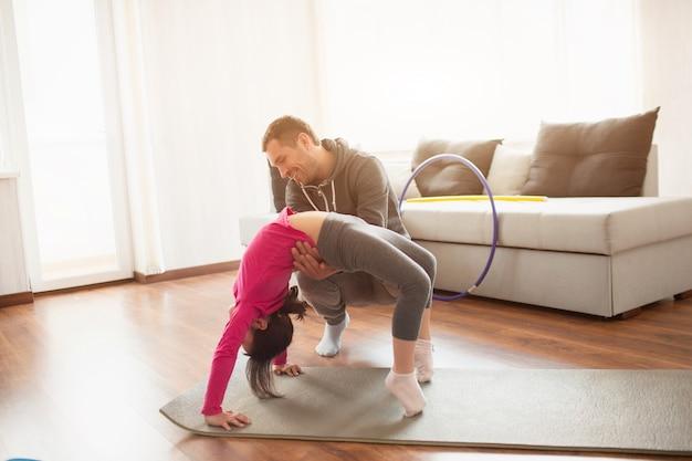 Le père et la fille s'entraînent à la maison. séance d'entraînement dans l'appartement. sports à la maison en pose de pont.