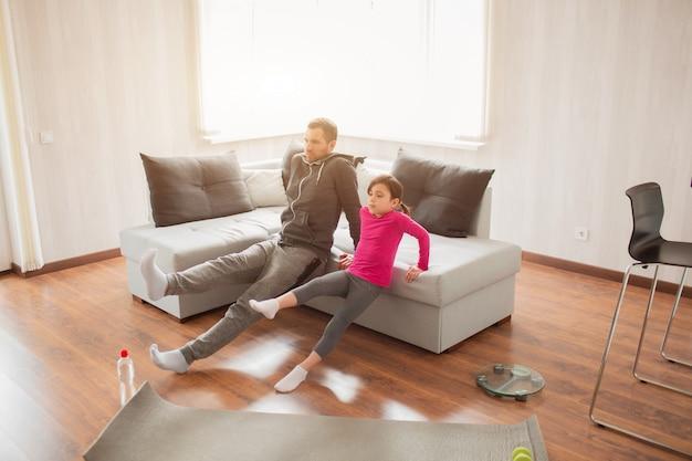 Le père et la fille s'entraînent à la maison. séance d'entraînement dans l'appartement. sports à la maison.