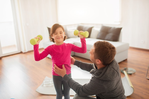 Le père et la fille s'entraînent à la maison. séance d'entraînement dans l'appartement.