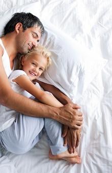 Père et fille se détendre sur le lit