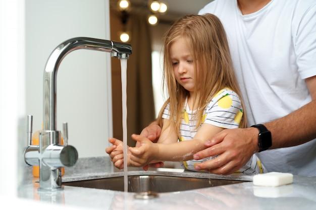 Père et fille se laver les mains au-dessus de l'évier dans une cuisine