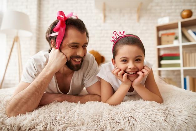 Père et fille sont couchés sur le lit.