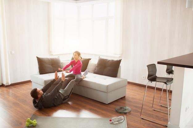 Le père et la fille suivent une formation sur les abdominaux à la maison. séance d'entraînement dans l'appartement.