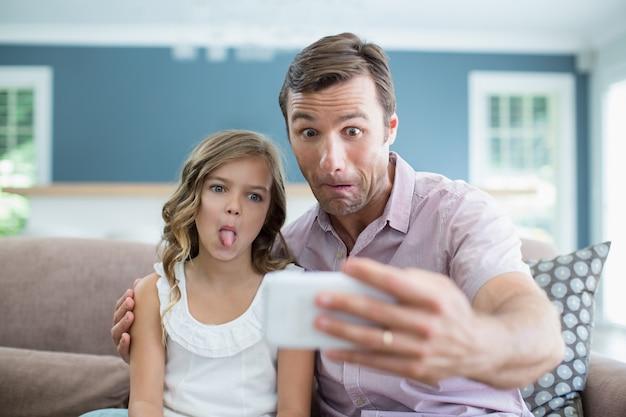 Père et fille tirant des grimaces tout en prenant selfie dans le salon