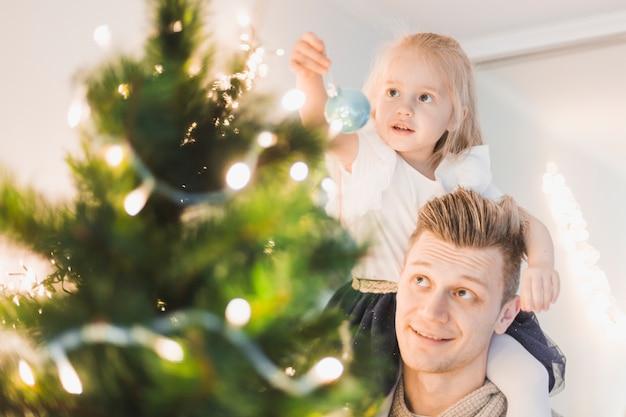 Père et fille touchant l'arbre de noël illuminé