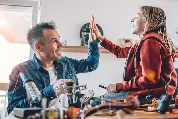 Père et fille travaillant sur des composants électroniques et acclamant