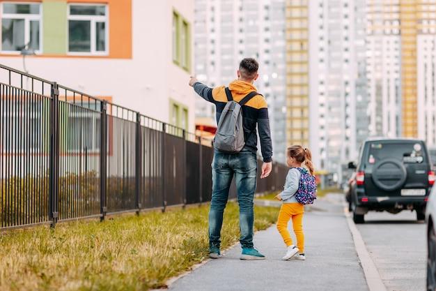 Père et fille vont à l'école pour la première fois. retour à l'école après la pandémie.