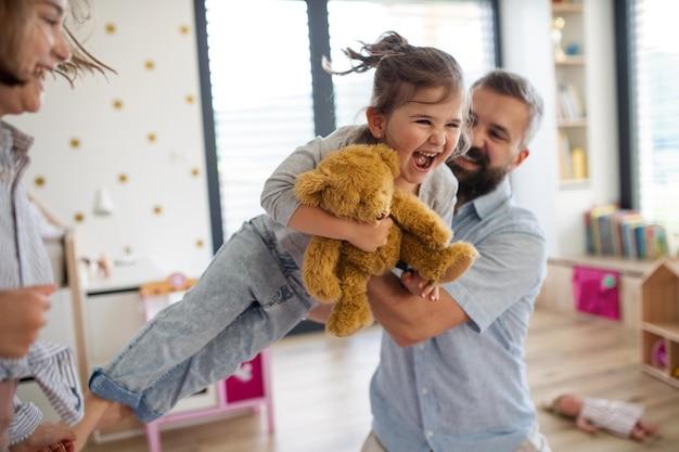 Père avec des filles à l'intérieur à la maison, jouant, riant et s'amusant.