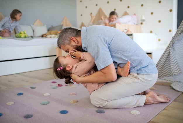 Un père avec des filles à l'intérieur à la maison, jouant, riant et s'amusant.