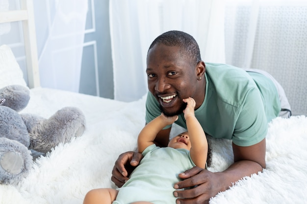 Père et fils afro-américains se blottissent et jouent à la maison sur le lit, famille heureuse, fête des pères