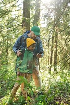 Père et fils à l'aide de téléphone portable comme boussole en marchant dans la forêt