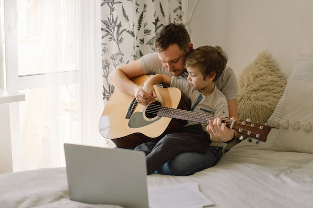 Père et fils apprennent à jouer de la guitare acoustique dans une leçon en ligne