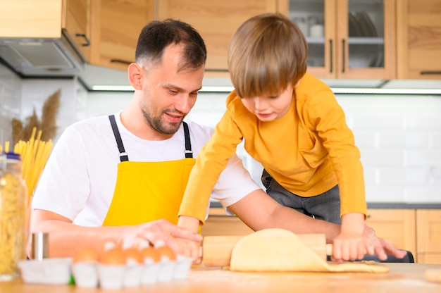 Père et fils en appuyant sur la pâte avec la pagaie