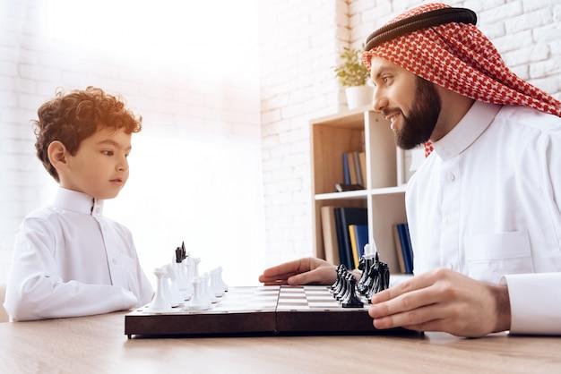 Un père et un fils arabes jouent aux échecs. loisirs en famille.