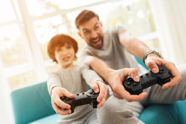 Père et fils assis et jouant sur console.