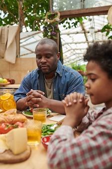 Père et fils assis à table et priant ensemble avant le dîner en famille