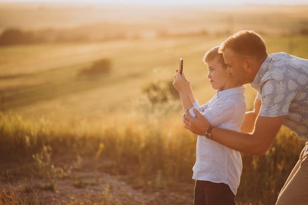 Père avec fils au coucher du soleil dans le parc