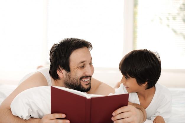 Père et fils au lit, lecture de livre ensemble
