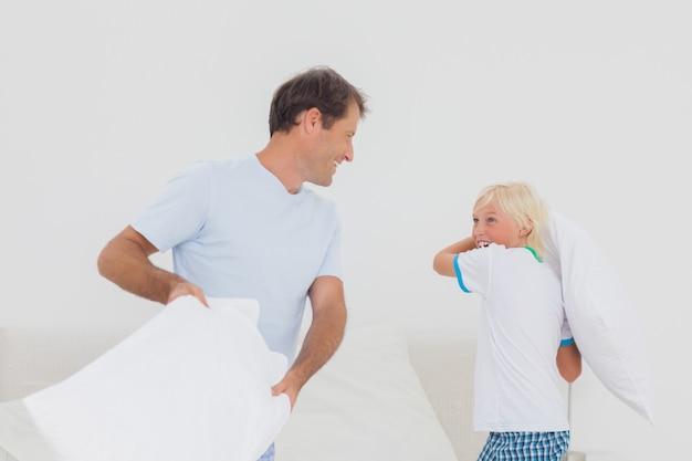 Père et fils ayant une bataille d'oreillers