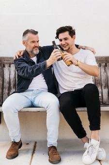 Père et fils sur le banc avec de la bière