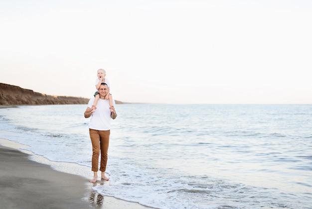 Père avec un fils blond sur ses épaules se promenant au bord de la mer, vacances en famille