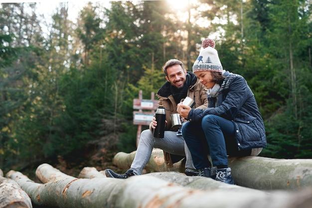 Père et fils buvant du thé chaud dans la forêt d'automne