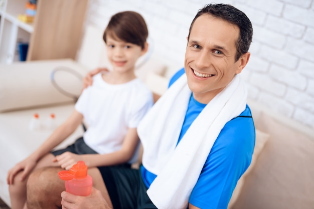Père et fils sur le canapé avec des bouteilles d'eau dans les mains